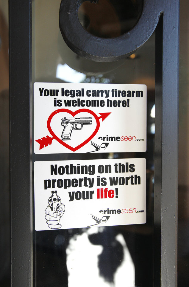 Photo - Stickers on the front door of Casa De Los Milagros Mexican Restaurant and Cantina in Oklahoma City communicate the establishment's firearms policy.  PAUL B. SOUTHERLAND - PAUL B. SOUTHERLAND