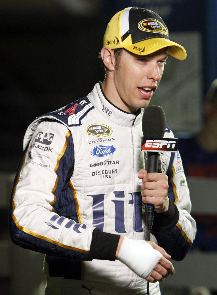 Photo - Brad Keselowski does an interview with a bandaged hand which he injured while celebrating his win in the NASCAR Sprint Cup series auto race Saturday, June  28, 2014, at Kentucky Speedway in Sparta, Ky. Keselowski cut his hand on a broken champagne bottle. (AP Photo/James Crisp)