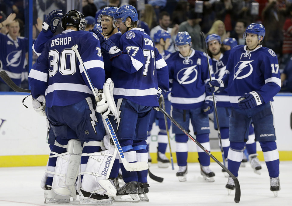 Photo - Tampa Bay Lightning goalie Ben Bishop (30) celebrates with teammates, including Victor Hedman (77), of Sweden, after stopping all the Ottawa Senators shots during a shootout in an NHL hockey game Thursday, Jan. 23, 2014, in Tampa, Fla. The Lightning won the game 4-3. (AP Photo/Chris O'Meara)