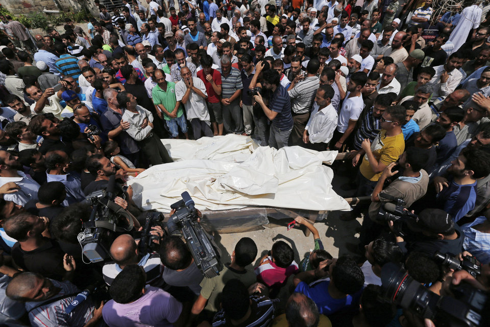 Photo - Mourners gather around the bodies of seven members of the Kelani family, killed overnight by an Israeli strike in Gaza City, during their funeral in Beit Lahiya, northern Gaza Strip, on Tuesday, July 22, 2014. Ibrahim Kelani, 53, his wife Taghreed and their five children, were killed in the strike on a Gaza City highrise. Ibrahim's brother Saleh Kelani said Tuesday that his brother and his brother's children, ranging in age from four to 12, had German citizenship, while his wife had not. The family had rented the apartment in the high-rise after fleeing their home in the northern Gaza town of Beit Lahiya which came under heavy shelling by the Israeli army. (AP Photo/Lefteris Pitarakis)