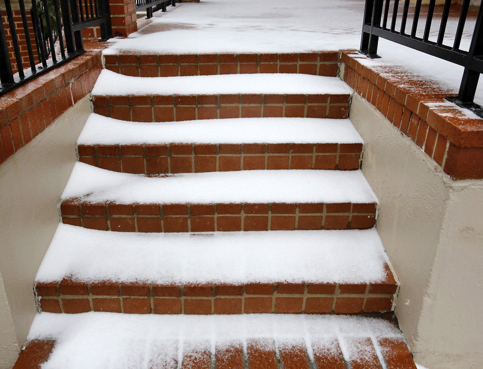 Snow partially covers the steps leading up to the entrance of a downtown church. Hundreds were served a traditional Christmas meal at the annual Red Andrews Dinner inside the Cox Convention Center on Christmas Day, Dec. 25, 2012. An army of  volunteers showed up despite  snow and ice and hazardous driving conditions. They accompanied each guest through the serving line and carried their trays and seated them at their tables. Other volunteers distributed a small mountain of toys and stuffed animals that were donated for the event.   Photo by Jim Beckel, The Oklahoman