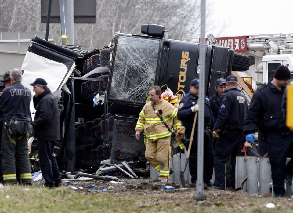 FILE - In this March 12, 2011 file photo, emergency personnel investigate the scene of a bus crash on Interstate 95 in the Bronx borough of New York. Ophadell Williams, the bus driver who with has been charged with 15 counts of manslaughter in the crash, will find out if he will face jail and a $250 thousand fine when the jury reads their decision in a New York City courtroom on Friday, Dec. 7, 2012. (AP Photo/David Karp, File)