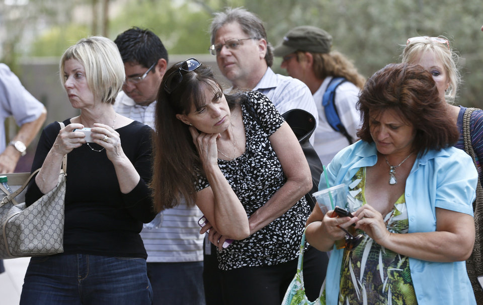 Photo - Curious onlookers check their cellphones and listen in on conversations in front of Maricopa County Superior Court Monday, May 6, 2013, in Phoenix. A Phoenix jury is on its second day of deliberations in the trial of Jodi Arias, who is accused of murdering her one-time boyfriend in Arizona. (AP Photo/Ross D. Franklin)
