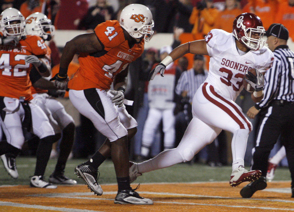 Photo - Oklahoma's Trey Millard (33) scores a touchdown in front of Oklahoma State's Orie Lemon (41) during the Bedlam college football game between the University of Oklahoma Sooners (OU) and the Oklahoma State University Cowboys (OSU) at Boone Pickens Stadium in Stillwater, Okla., Saturday, Nov. 27, 2010. Photo by Sarah Phipps, The Oklahoman