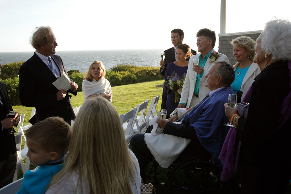 Photo - In this Sept. 21, 2013 photo, Erling Thorgalsen, at left, makes a toast in honor of his sister, Helen, second right, and Bonnie Clement, fourth right, after their wedding, as longtime friends former President George H.W. Bush, seated third right, and former first lady Barbara Bush, right, listen, in Kennebunkport, Maine. Bush was an official witness at the same-sex wedding, his spokesman said Wednesday, Sept. 25, 2013. (AP Photo/Susan Biddle)