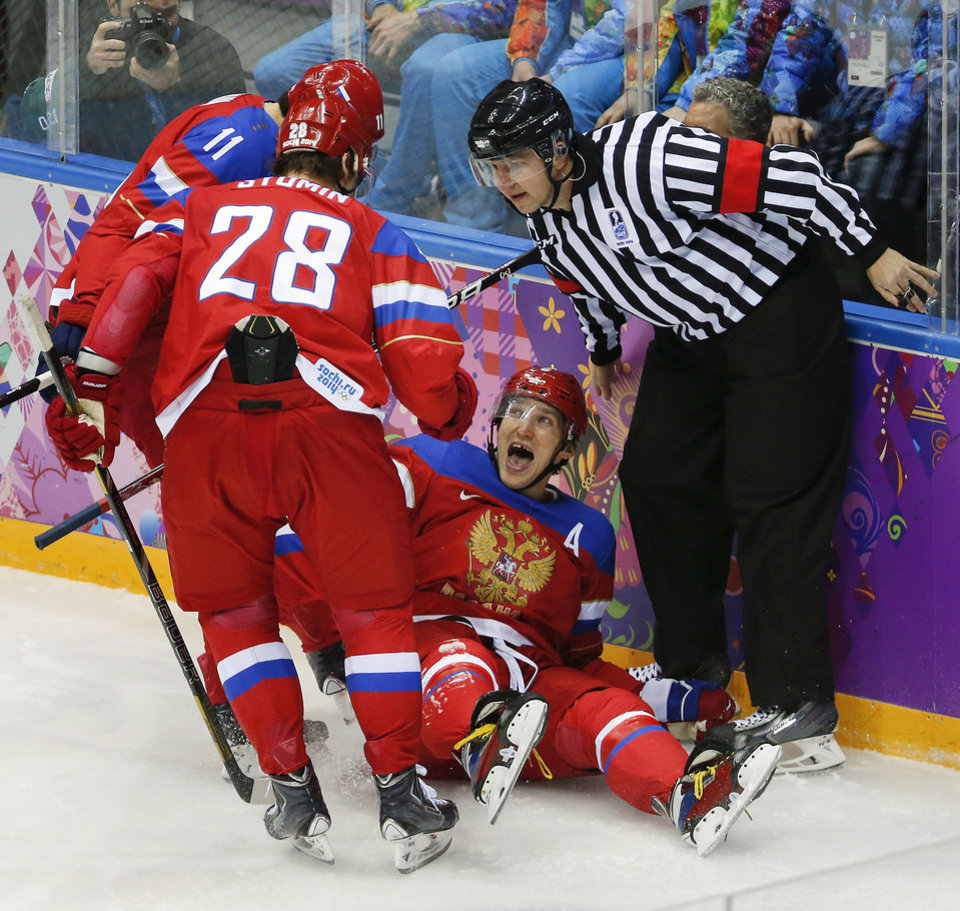 Photo - Russia forward Alexander Ovechkin reacts with forward Alexander Syomin and forward Yevgeni Malkin after scoring a goal against Slovenia in the first period of a men's ice hockey game at the 2014 Winter Olympics, Thursday, Feb. 13, 2014, in Sochi, Russia. (AP Photo/Mark Humphrey, File)