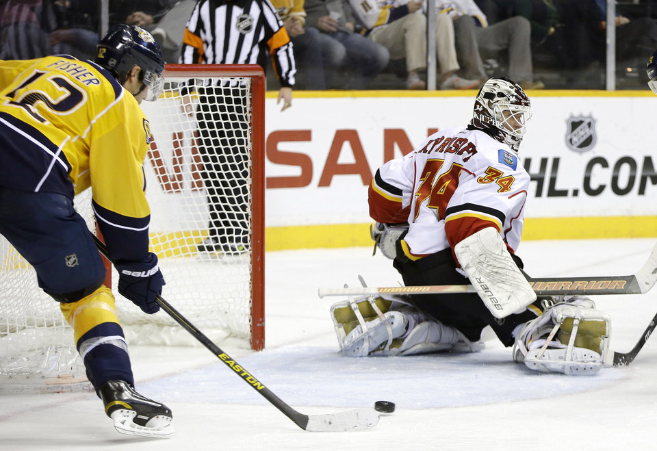 Nashville Predators center Mike Fisher (12) scores against Calgary Flames goalie Miikka Kiprusoff (34), of Finland, in the second period of an NHL hockey game, Thursday, March 21, 2013, in Nashville, Tenn. (AP Photo/Mark Humphrey)