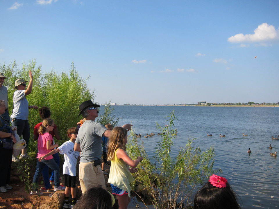 Young members of Temple B'nai Israel and Emanuel Synagogue, along with their parents and other adults, toss breadcrumbs into the water during a recent Tashlich service at Lake Hefner in Oklahoma City. The service  traditionally is held around a body of water during the Jewish High Holy Days. <strong>Carla Hinton - The Oklahoman</strong>
