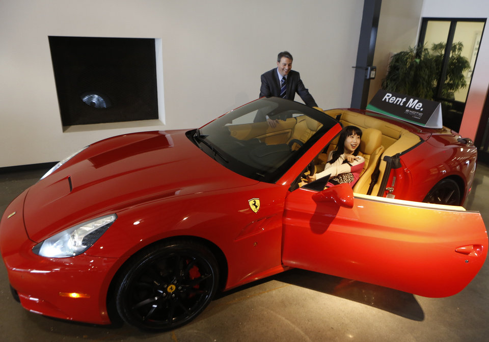 Photo - In this Wednesday, March, 26, 2014 photo, Adam Belsky, Enterprise Exotic Car Collection manager shows Jingyi Yang, 21, from Seattle a 2014 Ferrari California displayed for rent at the Enterprise Exotic Car Collection showroom near Los Angeles International Airport. (AP Photo/Damian Dovarganes)