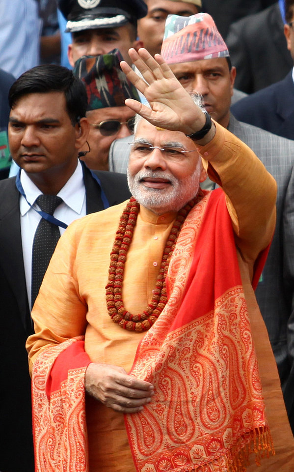 Photo - Indian Prime Minister Narendra Modi, waves to the crowd as he leaves after offering prayers at the Pashupatinath Hindu Temple in Katmandu, Nepal, Monday, Aug. 4, 2014. Modi arrived in Nepal on Sunday to meet with top leaders, offer prayers at this revered Hindu temple and address parliament. (AP Photo/Kiran Panday)