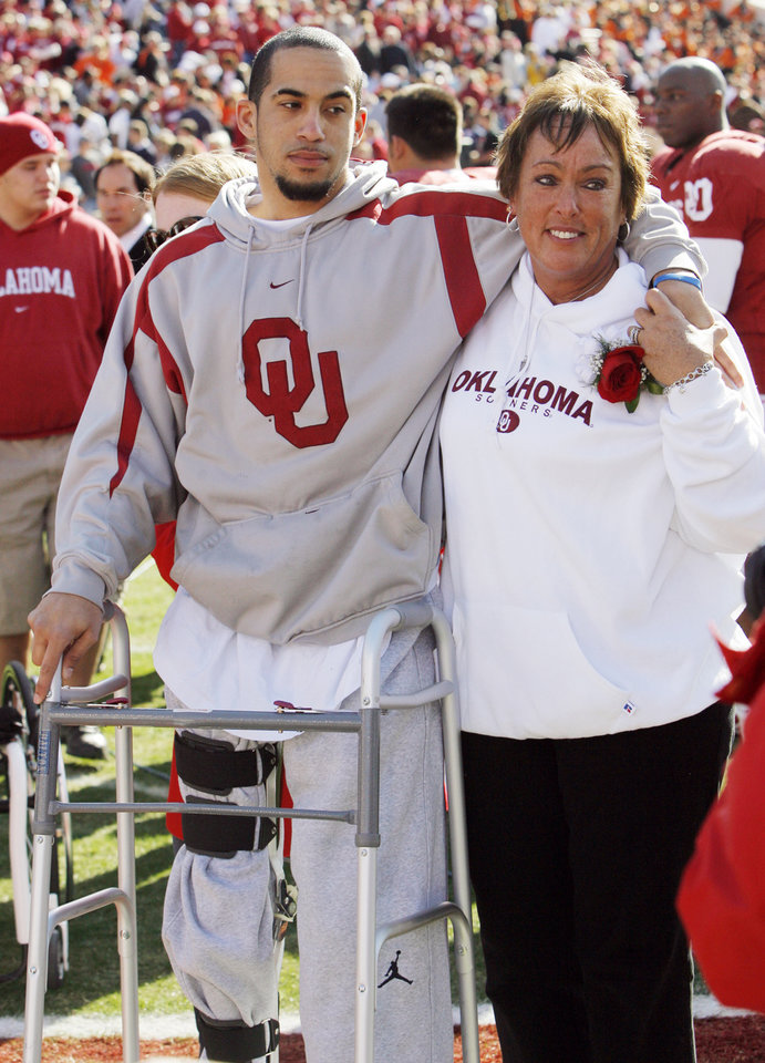 Photo - OU's Corey Wilson, left, stands with his mother, Wendy Wilson, before the Bedlam college football game between the University of Oklahoma Sooners (OU) and the Oklahoma State University Cowboys (OSU) at the Gaylord Family-Oklahoma Memorial Stadium on Saturday, Nov. 28, 2009, in Norman, Okla. Before the game Corey Wilson walked on Owen Field for the first time since a car wreck left him partially paralyzed in February. Photo by Nate Billings, The Oklahoman