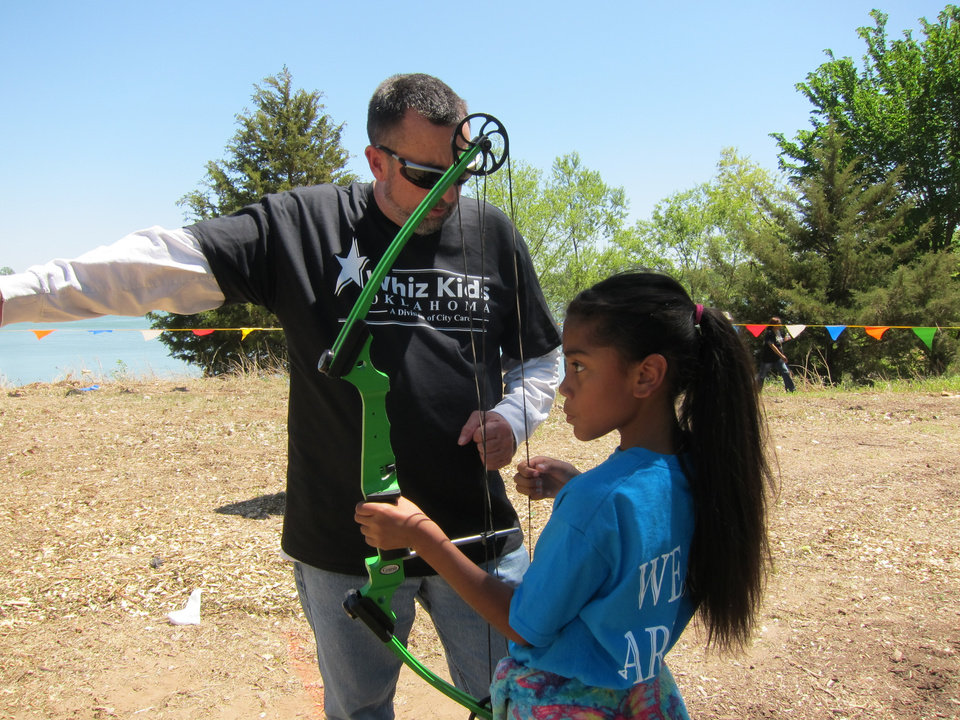"Photo -  Don Coffman, a Junior Olympic archery coach, helps Miriam Ford, 10, from Edgemere Elementary School, learn archery skills at the recent Whiz Kids ""Spring Fling"" event at Crystal Lake. Photo by Carla Hinton, The Oklahoman"