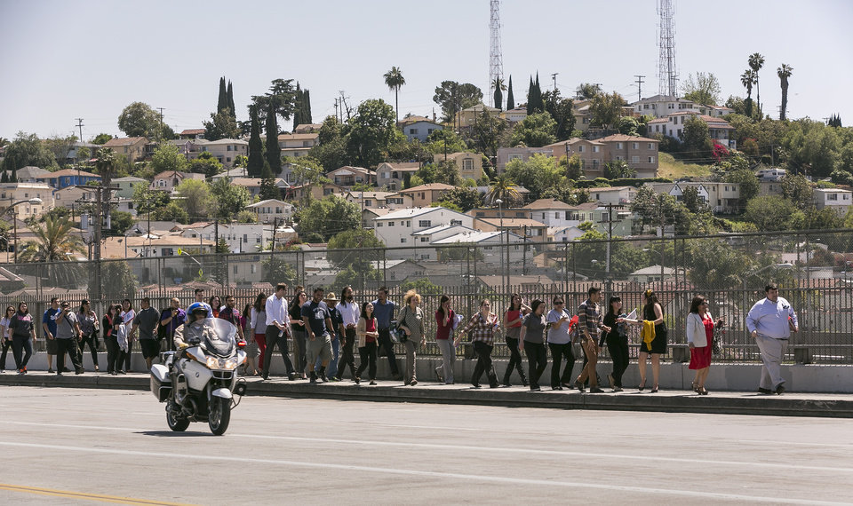 A California Highway Patrol officer escorts students back to Cal State University Los Angeles campus, after a mandatory evacuation on a report of a suspicious item, according to the Los Angeles Police Department in Los Angeles Thursday, April 18, 2013. Two telephoned bomb threats prompted officials at Cal State Los Angeles today to cancel afternoon classes and evacuate the campus. (AP Photo/Damian Dovarganes)