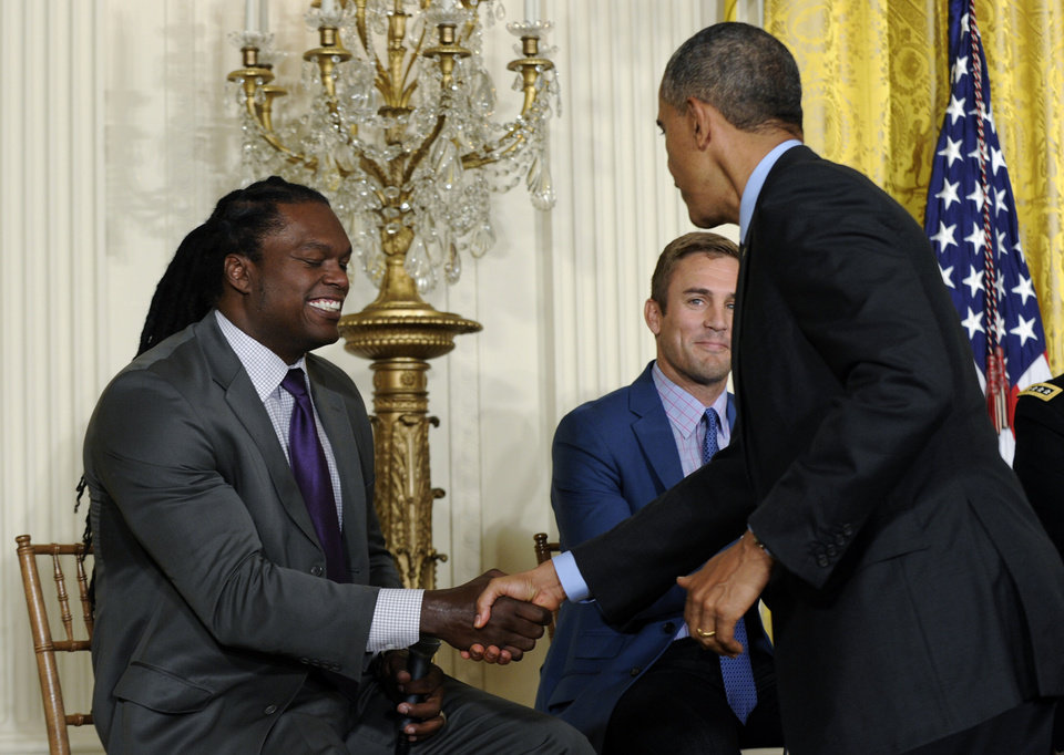 Photo - President Barack Obama shakes hands with former football player Lavar Arrington, left, as former professional soccer player and current ESPN analyst Taylor Twellman watches at center, after Obama spoke at the White House Healthy Kids & Safe Sports Concussion Summit, Thursday, May 29, 2014, in the East Room of the White House in Washington. Obama was hosting the summit with representatives of professional sports leagues, coaches, parents, young athletes, researchers and others to call attention to the issue of youth sports concussions. (AP Photo/Susan Walsh)