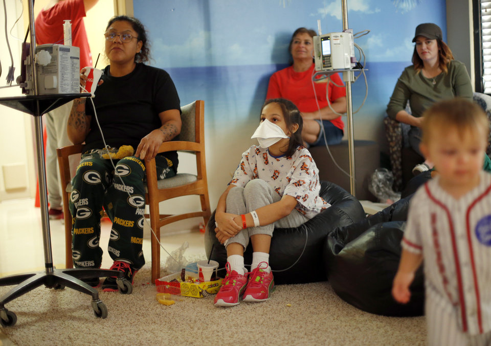 Photo -  Evangeline Carter, 10, a patient at The Children's Hospital at OU Medical Center, watches a movie with her mother, Cristina Chaino-Ahkeahbo, on the 10th floor of the hospital in Oklahoma City. 10 Strong, a group of parents of patients, raises money to hold events like movie night every few weeks at the hospital. [Photo by Bryan Terry, The Oklahoman]