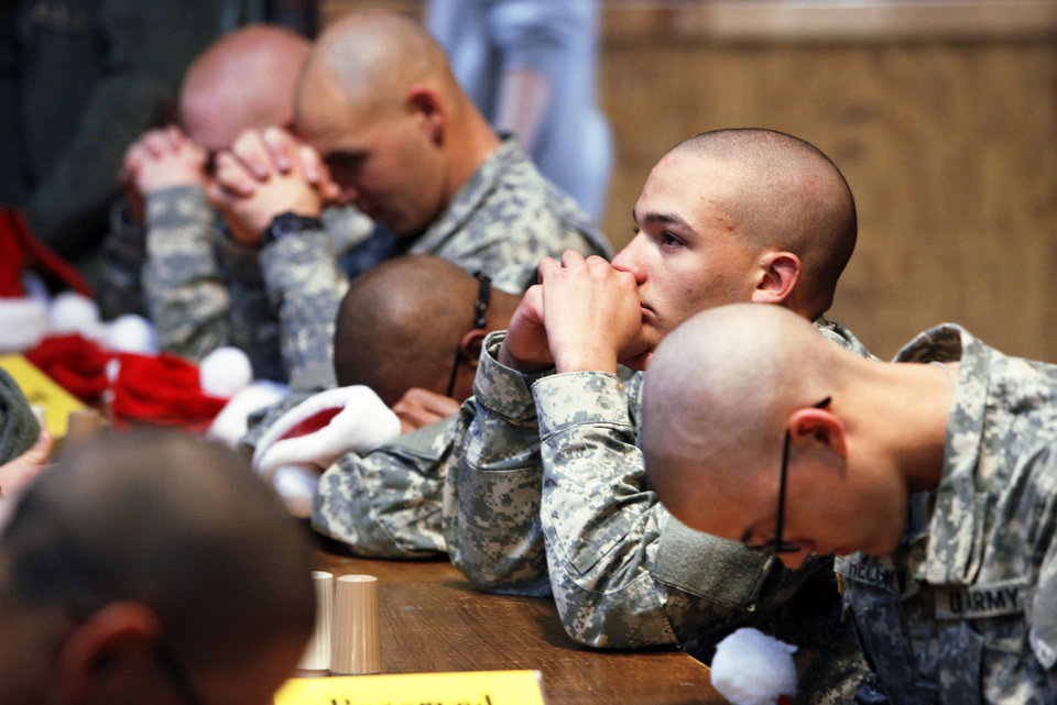 Photo - Above: Recruits pray before lunch Friday at Gattitown during Soldiers Day Out.
