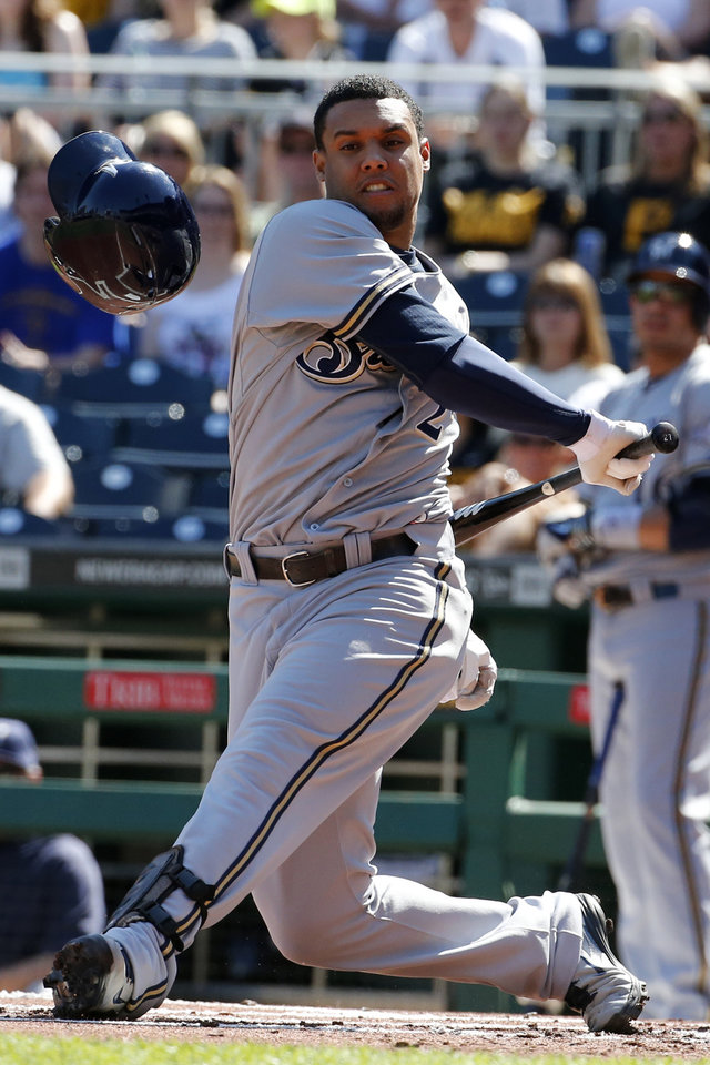 Photo - Milwaukee Brewers' Carlos Gomez (27) swings out of his helmet during the first inning of a baseball game against the Pittsburgh Pirates in Pittsburgh Saturday, June 7, 2014. (AP Photo/Gene J. Puskar)