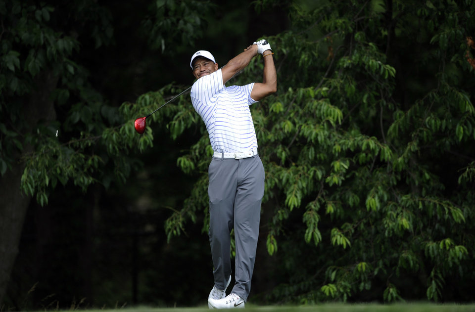 Photo - Tiger Woods watches his tee shot on the sixth hole during the Pro-Am at the Quicken Loans National golf tournament, Wednesday, June 25, 2014, in Bethesda, Md. (AP Photo/Nick Wass)