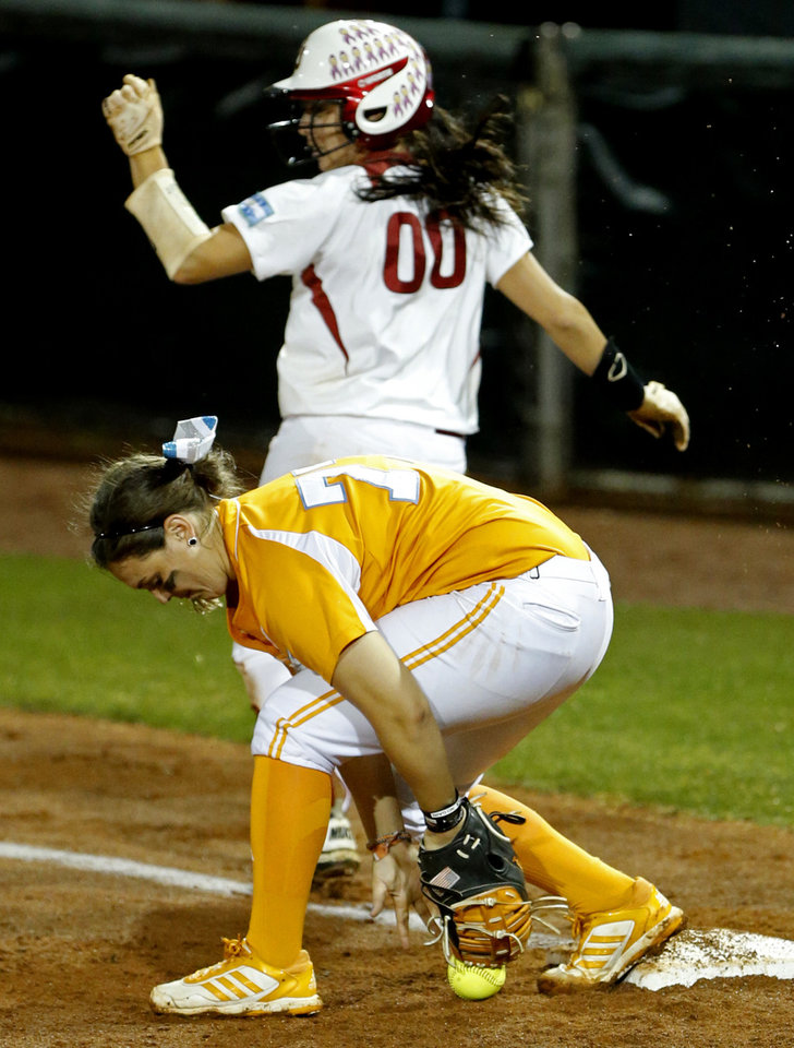 Photo - Tennessee's Cheyanne Tarango can't handle the ball on the throw to first and Oklahoma's Destinee Martinez is safe as the University of Oklahoma Sooner (OU) softball team plays Tennessee in the first game of the NCAA super regional at Marita Hynes Field on May 23, 2014 in Norman, Okla. Photo by Steve Sisney, The Oklahoman