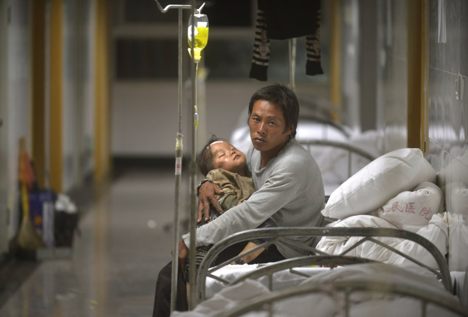 Photo - A man holds an injured child receiving medical treatment at a hospital following an earthquake in Ludian county in southwest China's Yunnan province Monday, Aug. 4, 2014. A strong earthquake in southern China's Yunnan province toppled thousands of homes on Sunday, killing hundreds and injuring more than a thousand people. (AP Photo) CHINA OUT