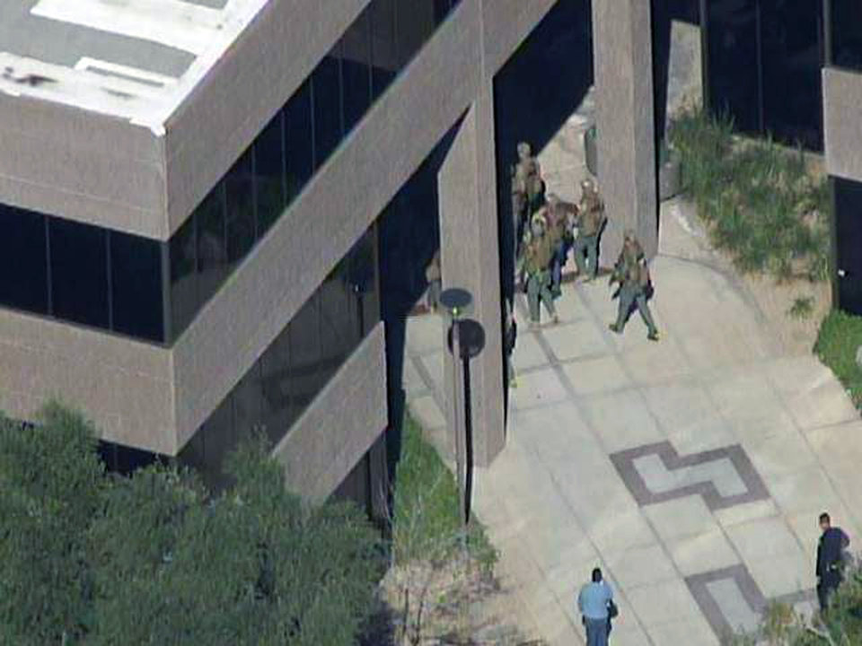 Photo - This frame grab provided by abc15.com shows the scene at a Phoenix office complex where police say a gunman shot at least three people on Wednesday, Jan. 30, 2013. Officer James Holmes said the victims were taken to hospitals and did not know if their injuries were life threatening. (AP Photo/abc15.com) MANDATORY CREDIT