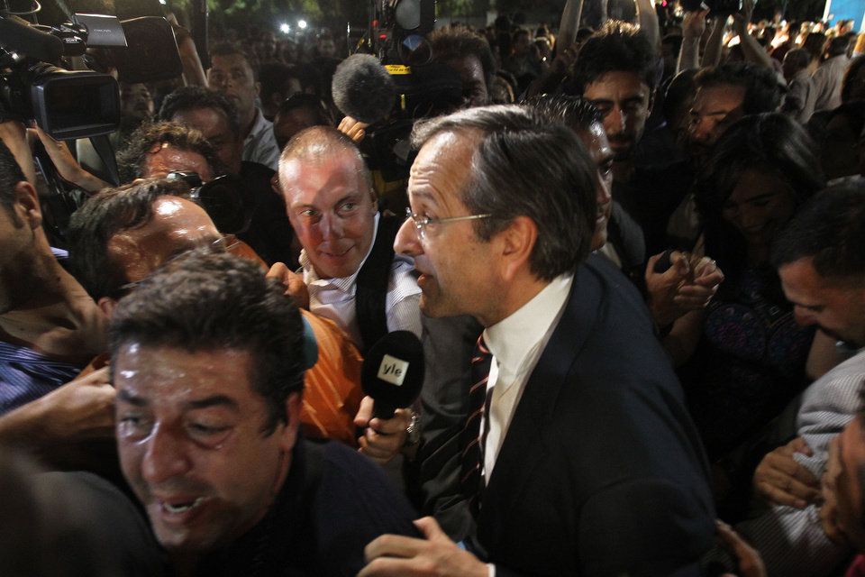 Photo -   Leader of the New Democracy conservative party Antonis Samaras surrounded by media, leaves an elections kiosk after speaking to his supporters at Syntagma square in Athens, late Sunday, June 17, 2012. The pro-bailout New Democracy party came in first Sunday in Greece's national election, and its leader has proposed forming a pro-euro coalition government. (AP Photo/Petros Karadjias)