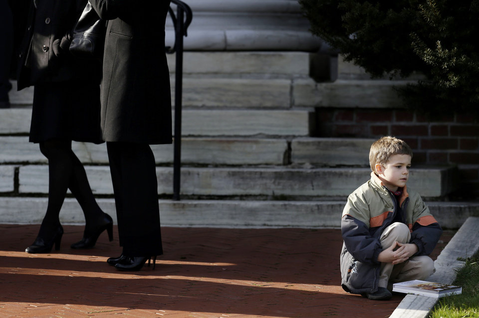 Photo - A boy sits near the steps of a church a church  before the memorial service for Lauren Rousseau in Danbury, Conn., Thursday, Dec. 20, 2012.   Rousseau, 30, was killed when Adam Lanza walked into Sandy Hook Elementary School in Newtown, Dec. 14, and opened fire, killing 26 people, including 20 children, before killing himself.  (AP Photo/Seth Wenig)