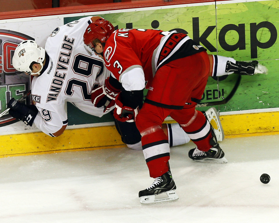Photo - Charlotte's Justin Krueger (3) checks Oklahoma City's Chris VandeVelde (29) into the boards in the first period during Game 1 of the AHL hockey playoff series between the Oklahoma City Barons and the Charlotte Checkers at the Cox Center in Oklahoma City, Friday, April 26, 2013. Photo by Nate Billings, The Oklahoman
