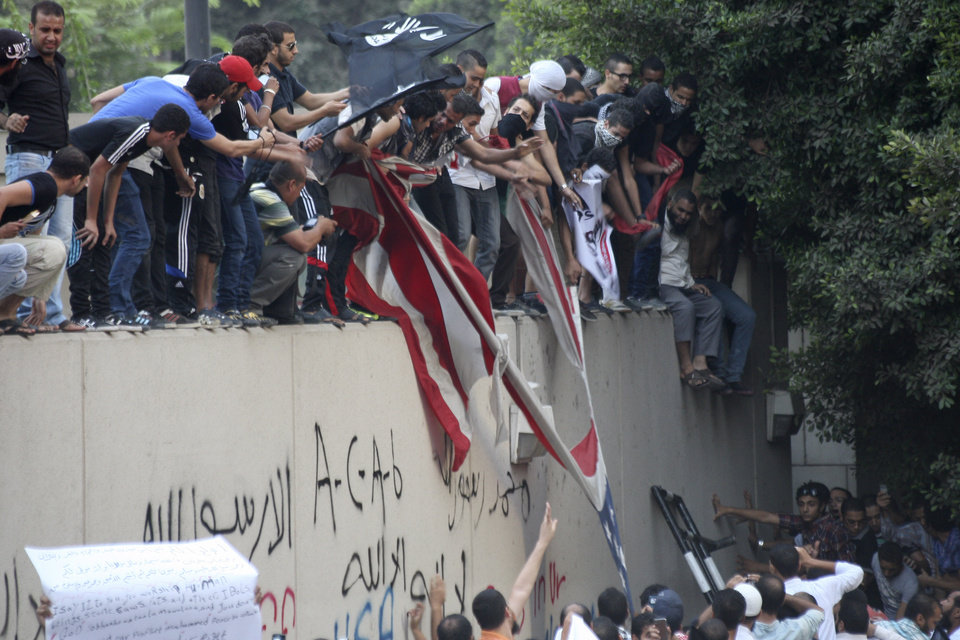 Photo -   Protesters destroy an American flag pulled down from the U.S. embassy in Cairo, Egypt, Tuesday, Sept. 11, 2012. Egyptian protesters, largely ultra conservative Islamists, have climbed the walls of the U.S. embassy in Cairo, went into the courtyard and brought down the flag, replacing it with a black flag with Islamic inscription, in protest of a film deemed offensive of Islam. (AP Photo/Mohammed Abu Zaid)