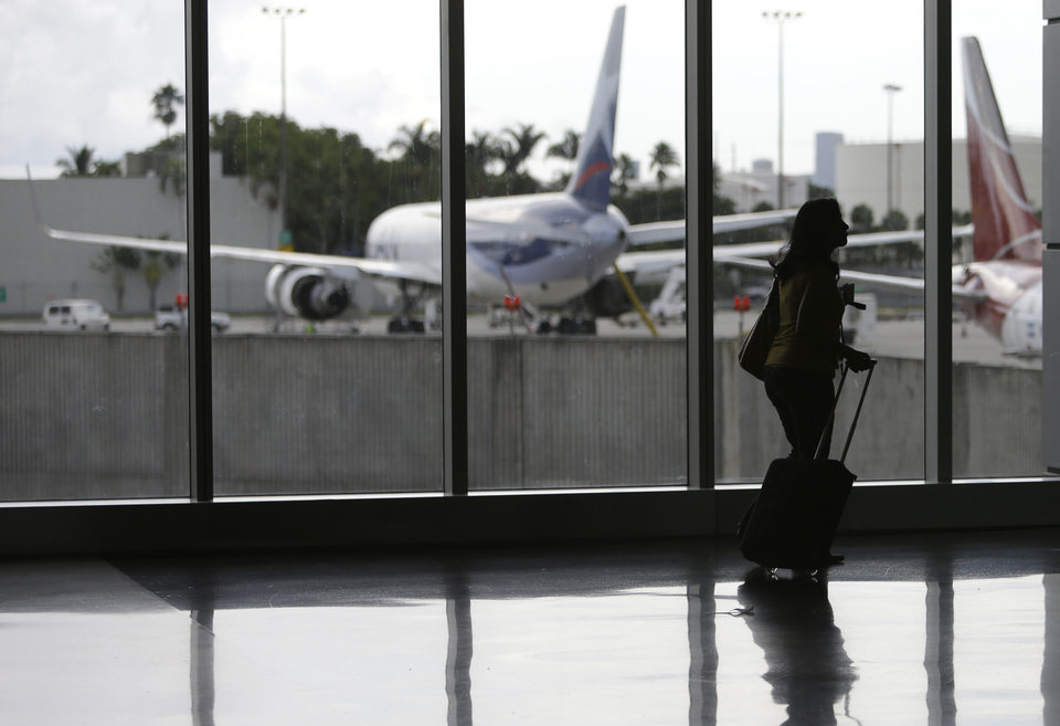 FILE-In this Thursday, Sept. 27, 2012, file photo, a passenger walks through the south terminal at Miami International Airport in Miami. U.S. companies are continuing to cut back on employee travel plans amid uncertainty surrounding the health of the economy. Americans are expected to take 438.1 million business trips this year, down 2 percent from last year, the Global Business Travel Association said Tuesday, Oct. 9, 2012. (AP Photo/Lynne Sladky)