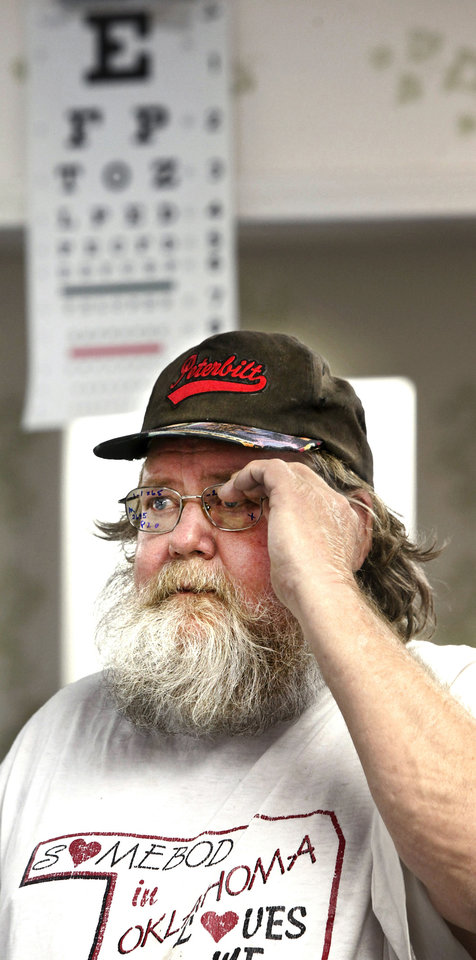 Photo - Leslie Miller, of Oklahoma City, puts on his new glasses to read an eye chart.  Photo by Jim Beckel, The Oklahoman