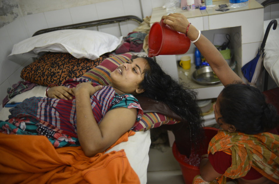 Photo - A family member washes the hair of Bangladeshi garment worker Ratna Rani, who broke her back in the garment factory building collapse, at a hospital in Savar, near Dhaka, Thursday, May 9, 2013. The death toll from the collapse of a garment factory building passed 900 on Thursday even as a fire in an 11-story garment factory Wednesday night in Dhaka killed eight people, including a ruling-party politician and a top official in the country's powerful clothing manufacturers' trade group. (AP Photo/Ismail Ferdous)