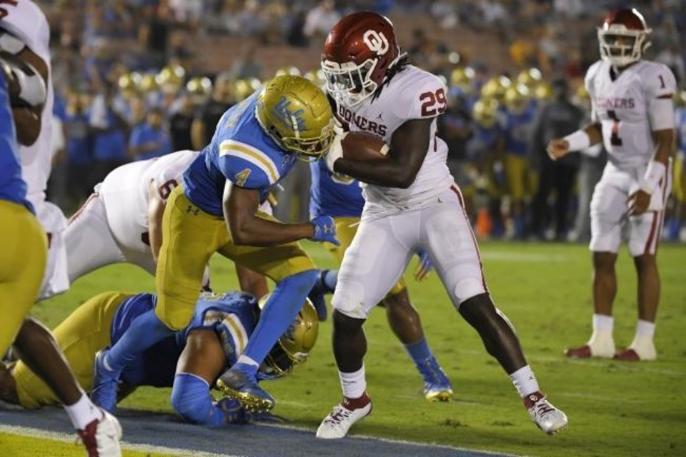 Photo -  Oklahoma running back Rhamondre Stevenson runs through UCLA defensive back Stephan Blaylock for a touchdown Saturday night in Pasadena, Calif. [AP Photo/Mark J. Terrill]