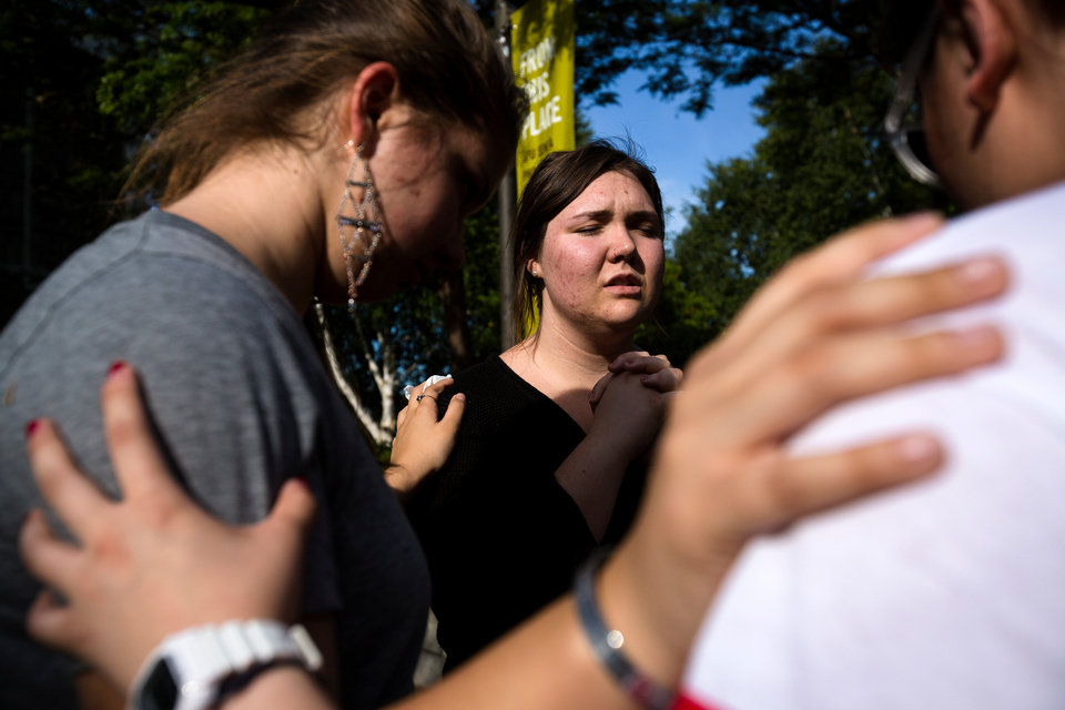 Photo - Following the lift of a lockdown in the wake of a school shooting, Seattle Pacific University students pray together Thursday, June 5, 2014, on the campus of Seattle Pacific University in Seattle, Wash. A gunman fatally wounded one young man and seriously injured a 20-year-old woman before being disarmed by a student worker at the small college. Three men and one woman were injured in the shooting, which started at 3:25 p.m. on SPU's Queen Anne neighborhood campus. One of the victims, a man in his 20s, died after being rushed to a hospital. (AP Photo/seattlepi.com, Jordan Stead)