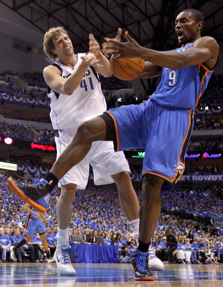 Oklahoma City's Serge Ibaka (9) fights for the ball with Dallas' Dirk Nowitzki (41) during Game 3 of the first round in the NBA playoffs between the Oklahoma City Thunder and the Dallas Mavericks at American Airlines Center in Dallas, Thursday, May 3, 2012. Photo by Bryan Terry, The Oklahoman