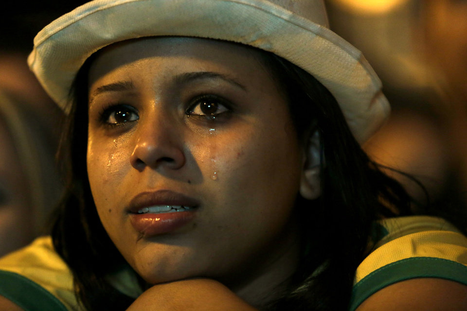 Photo - A Brazil soccer fan cries as she watches her team lose to Germany in a semifinal World Cup game on TV in Belo Horizonte, Brazil, Tuesday, July 8, 2014. (AP Photo/Bruno Magalhaes)