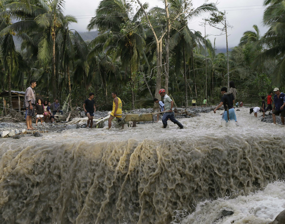 Residents cross a river with the body of a child after retrieving it from the flash flood-hit village of Andap, in New Bataan township, Compostela Valley in southern Philippines Wednesday, Dec. 5, 2012, a day after Typhoon Bopha made landfall. Typhoon Bopha, one of the strongest typhoons to hit the Philippines this year, barreled across the country\'s south on Tuesday, killing scores of people while triggering landslides, flooding and cutting off power in two entire provinces. (AP Photo/Bullit Marquez)