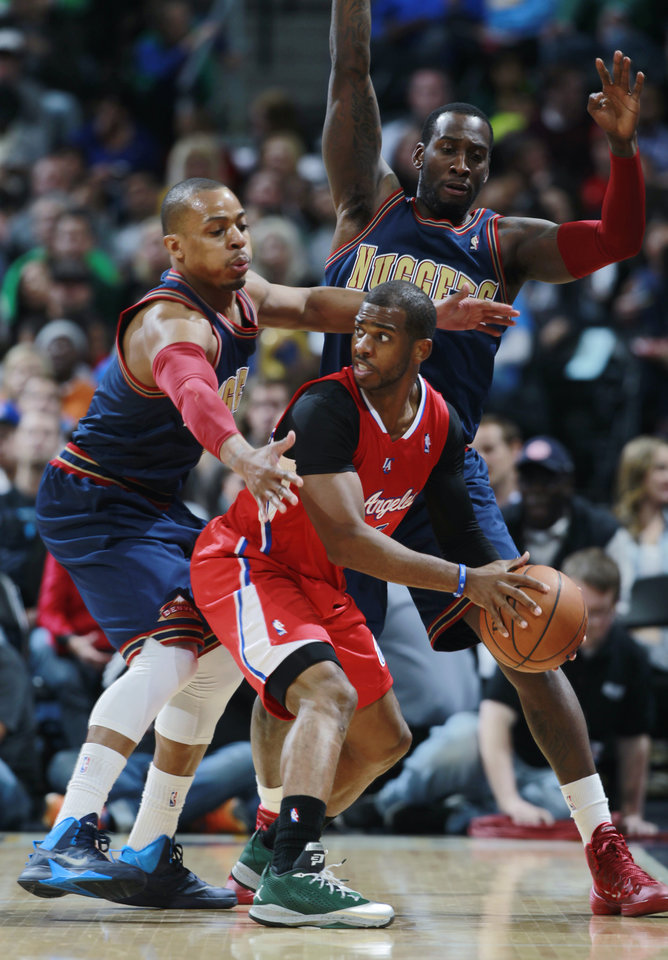 Photo - Los Angeles Clippers guard Chris Paul, front right, is trapped with ball by Denver Nuggets guard Randy Foye, front left, and forward J.J. Hickson in the second quarter of the Nuggets' 110-100 victory in an NBA basketball game in Denver on Monday, March 17, 2014. (AP Photo/David Zalubowski)
