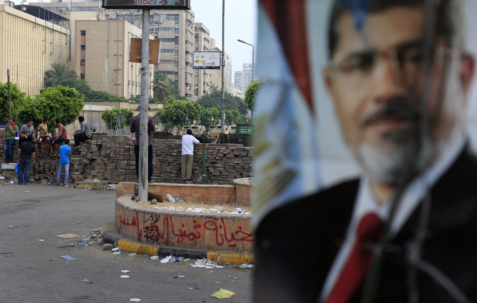 Photo - Supporters of ousted President Mohammed Morsi protest as army soldiers guard at the Republican Guard building in Nasr City, in Cairo, Egypt, Wednesday, July 10, 2013. (AP Photo/Hassan Ammar)