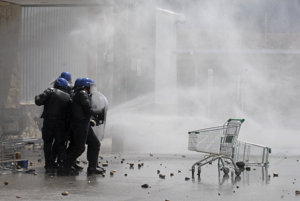 Amidst tear gas, police officers take cover from stones during clashes with looters at a supermarket in San Carlos de Bariloche, about 1.630 km southwest of Buenos Aires, Argentina, Thursday, Dec. 20, 2012. Hooded people looted at least three supermarkets and set a car on fire after claiming for food to celebrate Christmas in the city of Bariloche, part of Argentina\'s Patagonia region. (AP Photo/Diario Rio Negro)