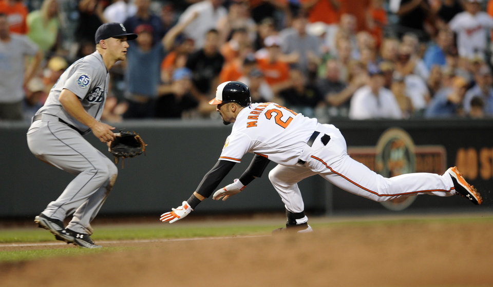 Photo -   Baltimore Orioles' Nick Markakis (21) heads for third on a triple as Seattle Mariners third baseman Kyle Seager waits for the ball during the third inning of a baseball game, Wednesday, Aug. 8, 2012, in Baltimore. (AP Photo/Nick Wass)