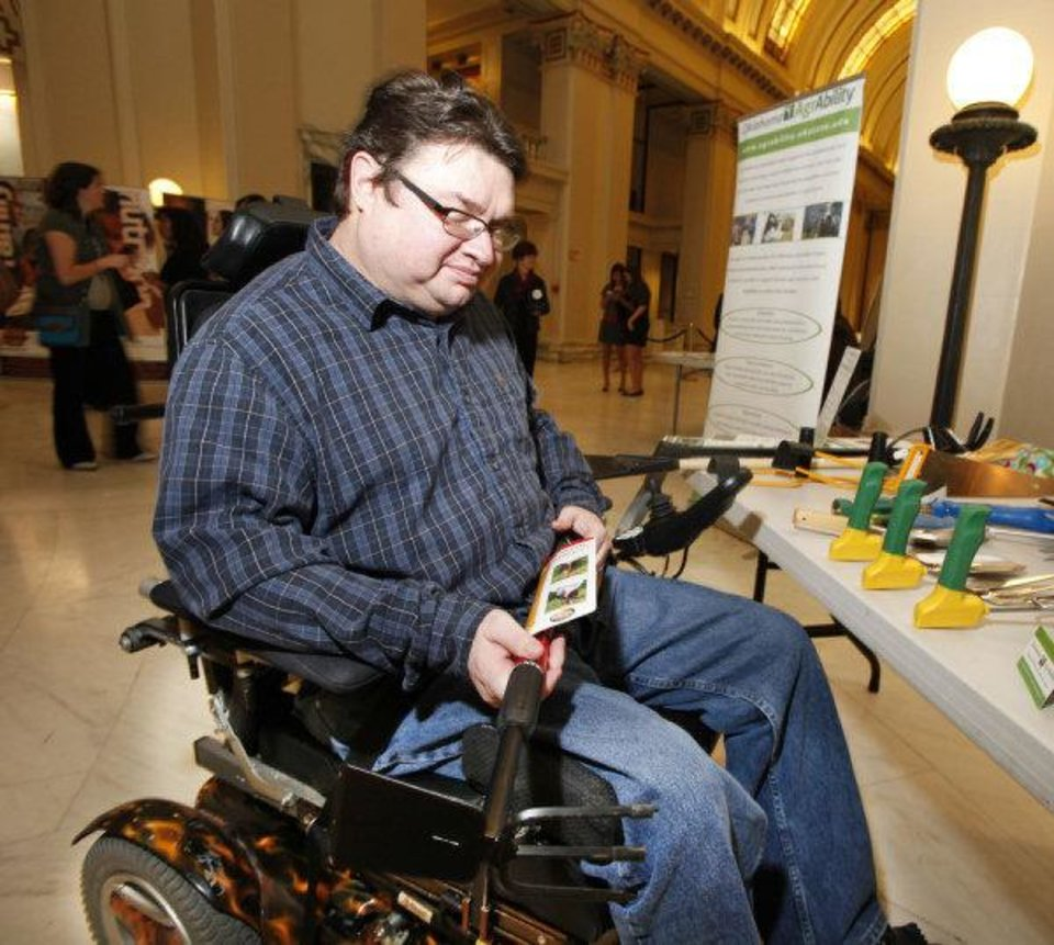 Philip Hampton looks at a modified garden tool during AgrAbililty Day at the State Capitol. <strong>Steve Gooch - The Oklahoman</strong>