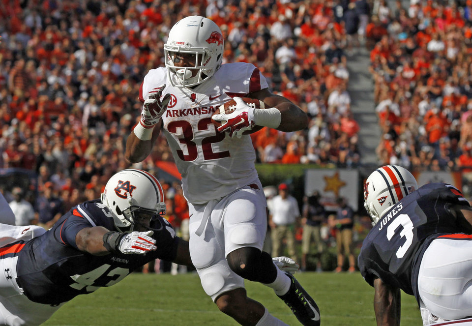 Photo - Arkansas running back Jonathan Williams (32) gets by Auburn linebacker Anthony Swain (43) and goes in for a touchdown during the first half of an NCAA college football game on Saturday, Aug. 30, 2014, in Auburn, Ala. (AP Photo/Butch Dill)