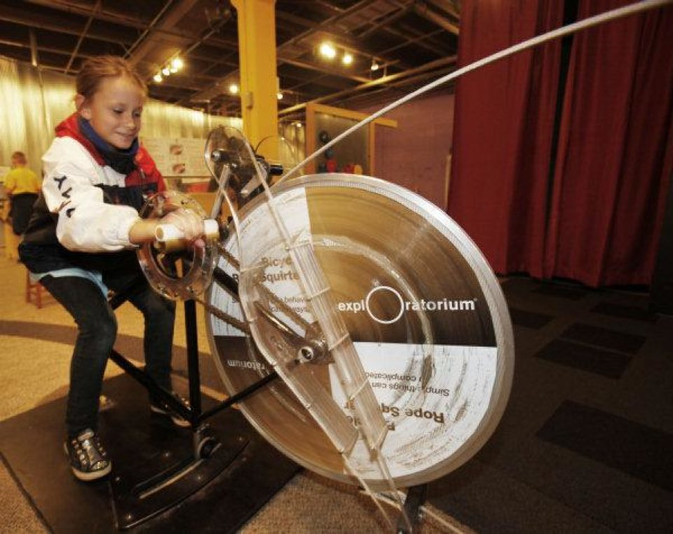 Azure Abbott, a fourth-grade student from Kaiser Elementary School, rides the Bicycle Rope Squirter at Science Museum Oklahoma. The museum celebrated Chemistry Day on Friday. Photo by Steve Gooch, The Oklahoman <strong></strong>