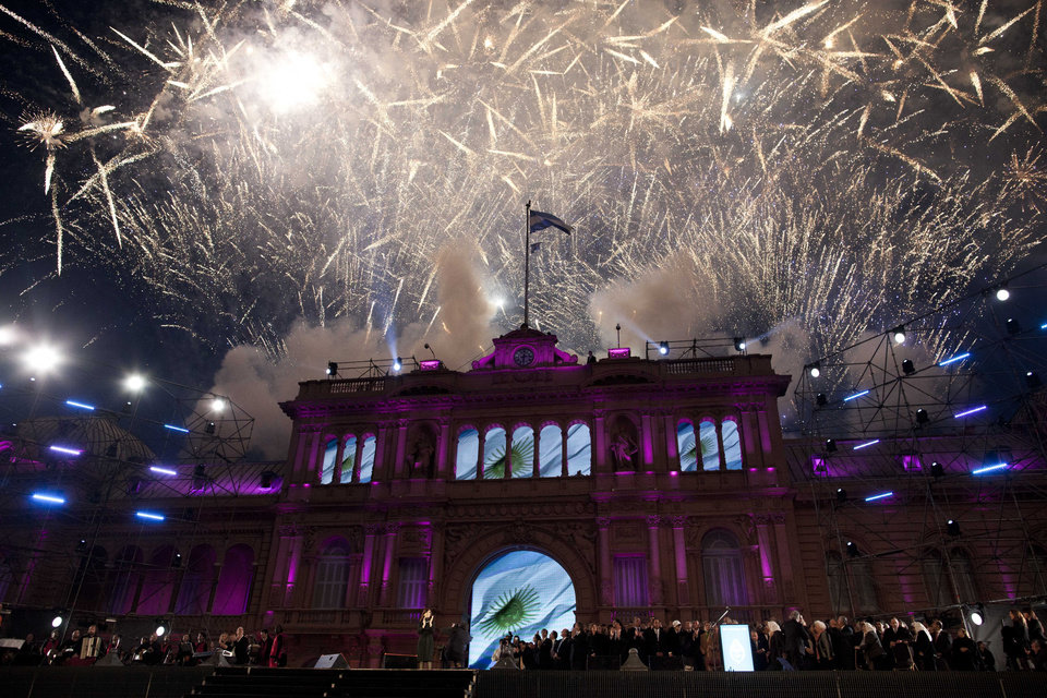 The government house is bathed in purple light as fireworks explode over a government rally in Buenos Aires, Argentina, Saturday, May 25, 2013. Cristina Fernandez\'s government and supporters are celebrating 10 years since she and her late husband Nestor Kirchner have held office, and the 203th anniversary of Argentina\'s May Revolution. (AP Photo/Natacha Pisarenko)