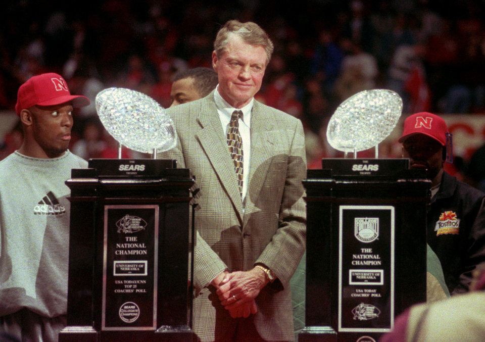 Photo - FILE - In this Jan. 3, 1996 file photo, Nebraska head football coach Tom Osborne stands between Nebraska's two National Championship trophies during the homecoming rally at the Devaney Sports Center in Lincoln, Neb. The Huskers won a third national title in 1997. Osborne will retire as Nebraska's athletic director on Jan. 1, 2013 and end an association with the university that began in 1962. (AP Photo/Dave Weaver, File)