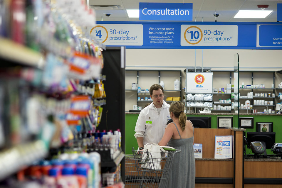 Photo - Jay Hungerford, pharmacy intern, speaks with a customer at Wal-Mart Neighborhood Market in Bentonville, Ark., Thursday June 5, 2014. Wal-Mart's supercenters still account for 80 percent of its 4,000-plus U.S. stores, but the retailer is opening smaller outlets that cater to shoppers looking for more convenience. It now plans to open 270 to 300 small stores during the current fiscal year — double its initial forecast.  (AP Photo/Sarah Bentham)