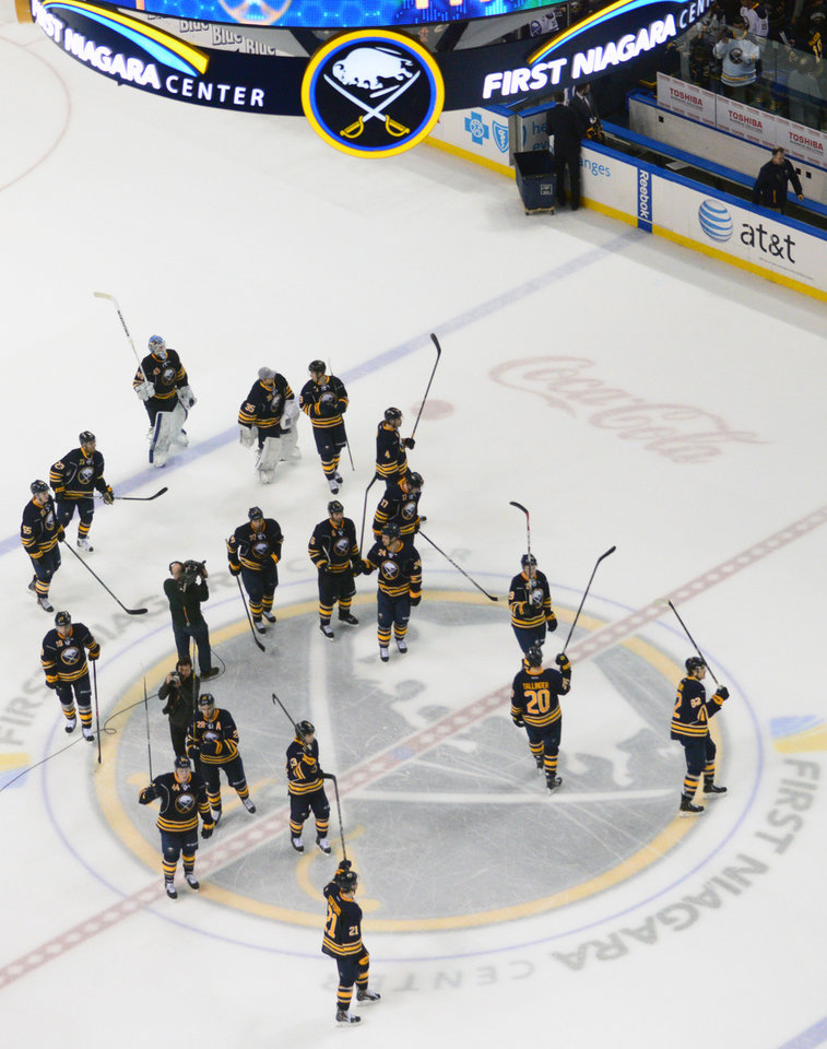 Photo - Buffalo Sabres gather at center ice to salute fans following their final regular season NHL hockey game against the New York Islanders' in Buffalo, N.Y., Sunday, April 13, 2014. (AP Photo/Adam Wiepert)