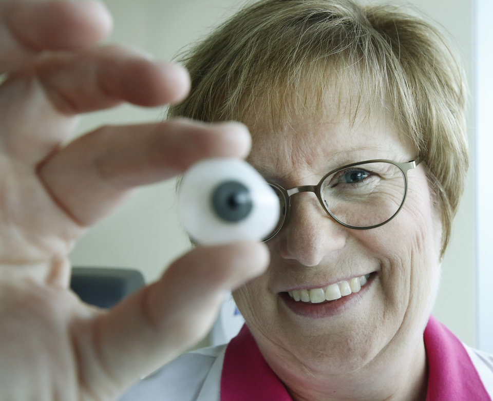 Photo -  Dean McGee Eye Institute Ocularist Nancy Lambert displays a prosthetic eye she made for a patient in Oklahoma City. Photo By Steve Gooch, The Oklahoman   Steve Gooch -  The Oklahoman