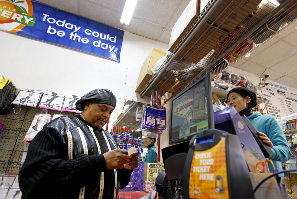 A customer, who declined to give his name, looks down at his Powerball lottery ticket after buying one at a convenience store, Wednesday, Nov. 28, 2012, in Atlanta, Ga. (AP Photo/David Goldman)